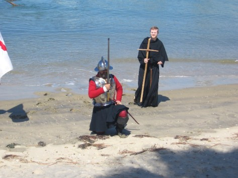 Cabrillo in armor raises his sword, while priest with cross stands behind him.