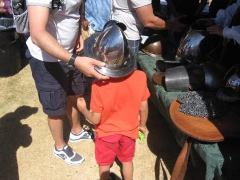 Small boy tries on a surprisingly heavy steel helmet.