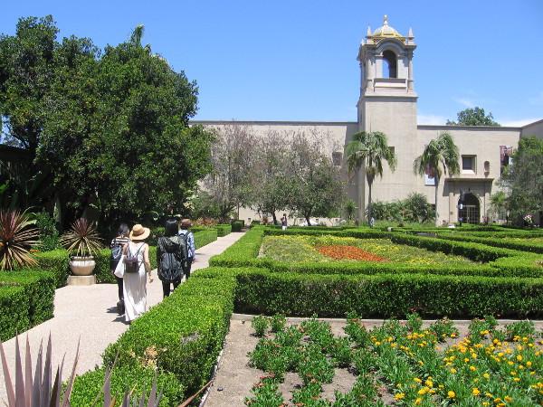 Visitors walk through Balboa Park's Alcazar Garden on a summer day.