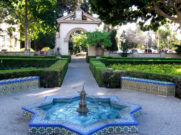 Moorish tiles on a fountain, colorful benches and an archway.