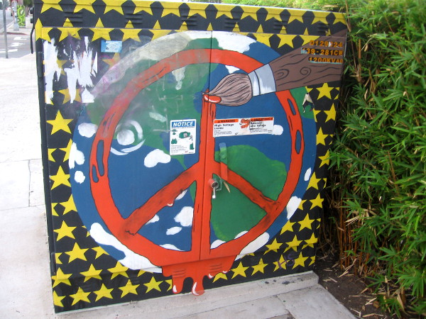 Peace symbol, planet Earth, paintbrush and stars on side of Hillcrest transformer.