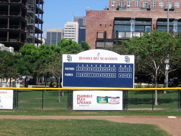 Scoreboard beyond outfield of tiny baseball diamond sponsored by Bumble Bee.