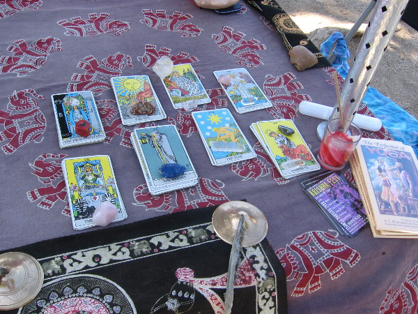 Table next to sidewalk features tarot cards kept in place by crystal paperweights.