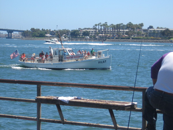 The Pilot with sightseeing tourists cruises past a pier on San Diego Bay.