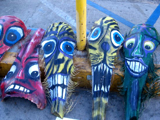 Whiskery, crazy, colorful faces painted on palm fronds.
