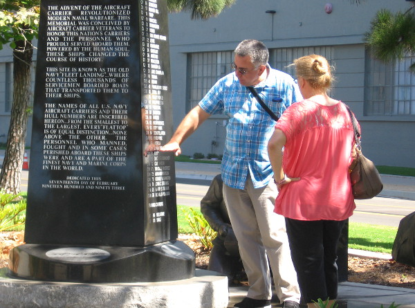 Man points out a recent fleet carrier name on the Aircraft Carrier Memorial.
