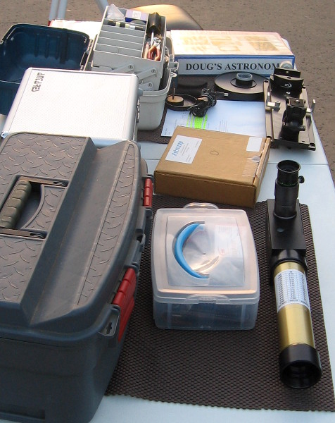 Table with astronomy book, eyepieces and other equipment.