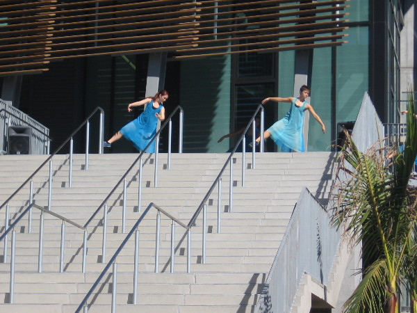 Dancers in flowing blue appear at the top of the broad steps!