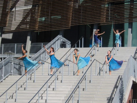Graceful dancers descend the high stairs in a grand entrance!