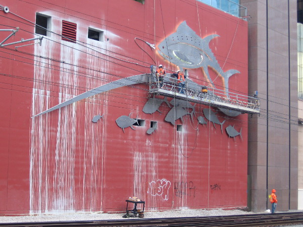 Workers on platform busy mounting a gigantic trophy fish to a high-rise building!