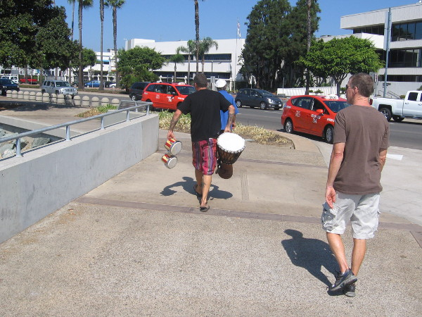 Boater walks along the Embarcadero with some drums.