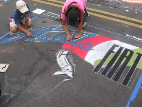 Team Arcala creating some chalk art that includes the Fiat logo.