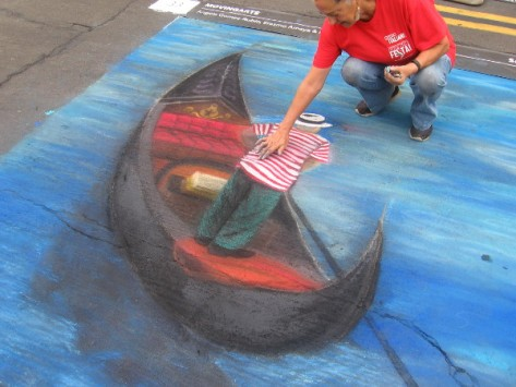 Movingarte is floating a chalk gondola on the dry asphalt canvas.