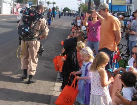 Kids get goodies from a ghostbuster patrolling El Cajon Boulevard.