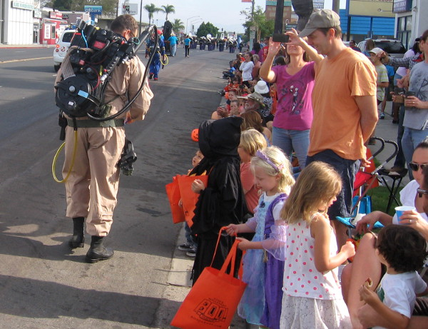 Kids get goodies from a ghostbuster patrolling El Cajon Boulevard.