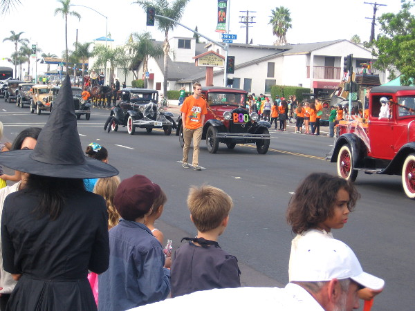 Here comes a long line of classic cars with spooky decorations.