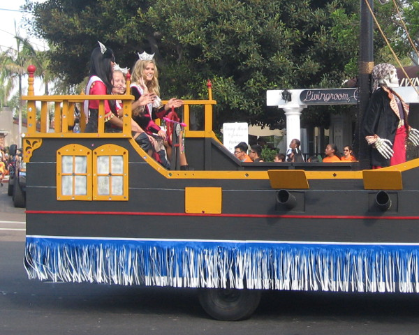 The second pirate ship rolls along with some waving beauty queens.