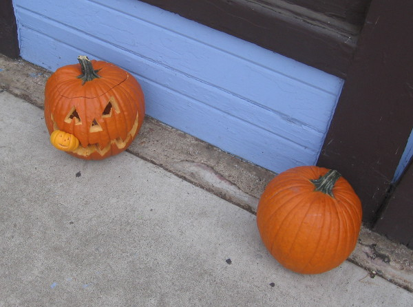 One pumpkin is devouring another in a festive nook in Balboa Park!