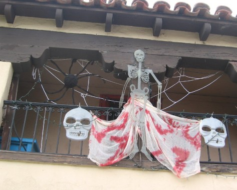 A studio in Spanish Village has skulls, spider and a skeleton hanging around.