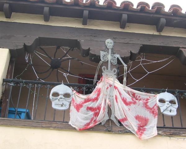 A studio in Spanish Village has skulls, spider and a skeleton hanging around.