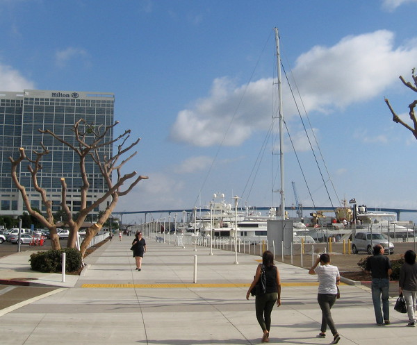 People walk toward Hilton hotel and giant mast of a world-record super yacht.