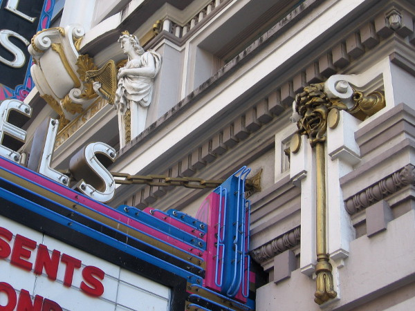 Classic theatrical figures above and beside the marquee.