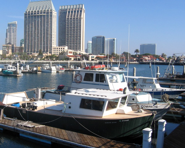 Hyatt, Marriott and Hilton rise behind Tuna Harbor fishing boats.
