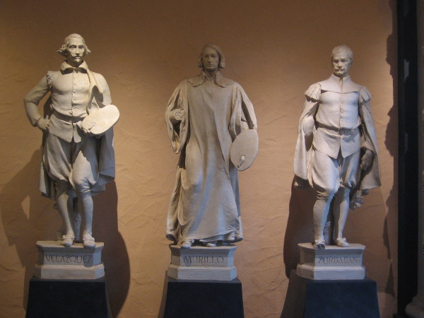 Plaster statues of Spanish painters become shadowy in courtyard of Casa del Prado.