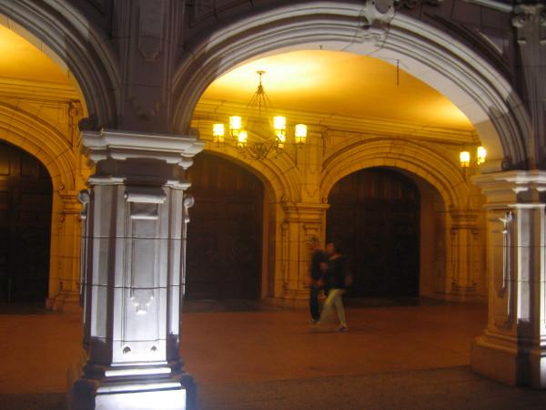 Walking down an elegant, golden corridor as night descends.