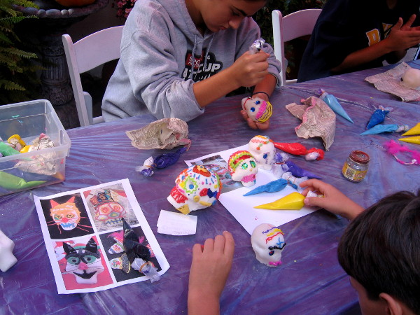 Kids decorate sugar skulls, a fun tradition of Day of the Dead.