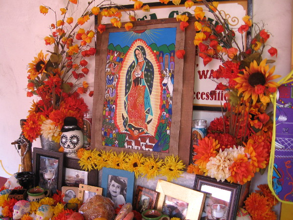 Altar at Fiesta de Reyes features Virgin Mary and photos of departed loved ones.
