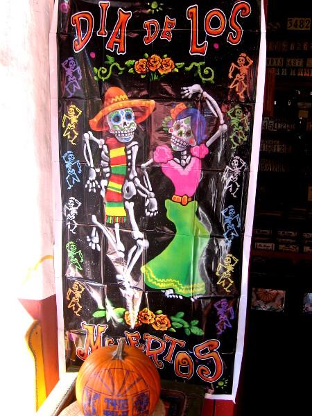 Fantastic sign above pumpkin shows lively, dancing skeletons.