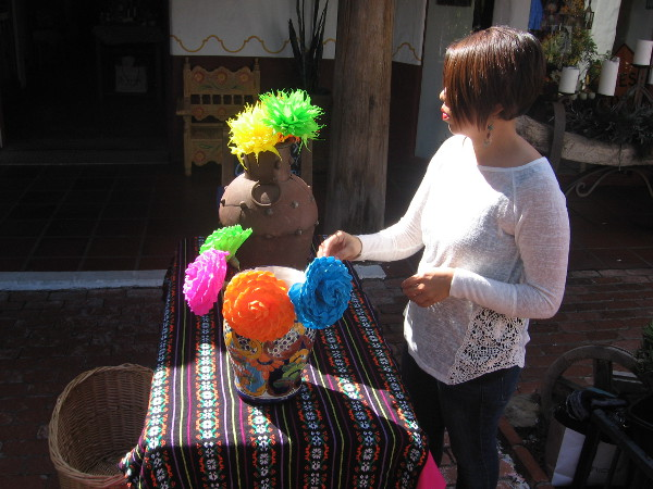 Lady in San Diego's Old Town arranges bright frilly flowers in the sun.