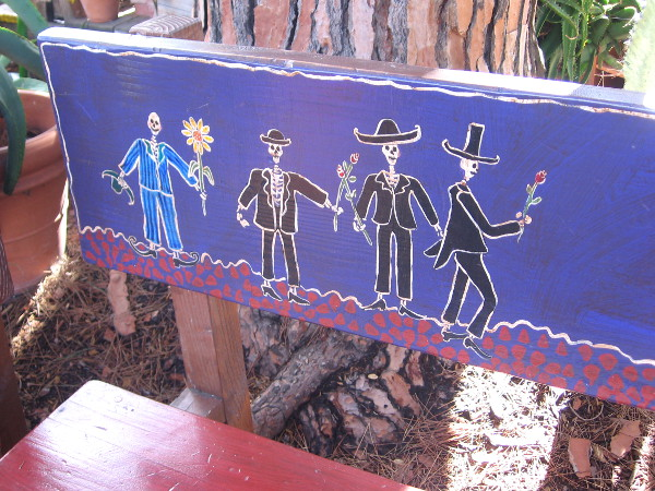 Bench at Fiesta de Reyes painted with sombrero-wearing, flower-bearing skeletons.