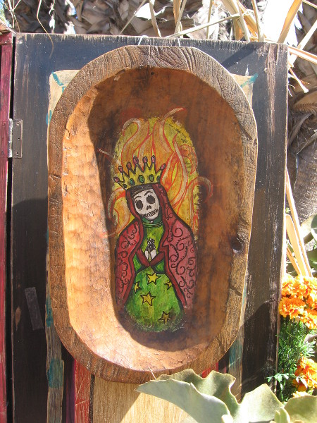 Small image in crude wooden frame in a larger altar.