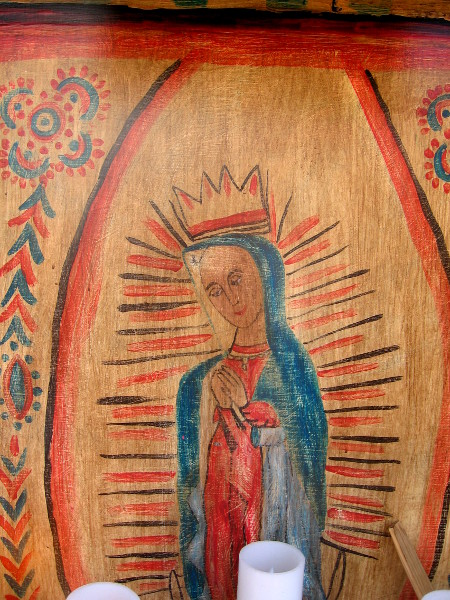 Radiant image of Virgin Mary on wood above altar candles.