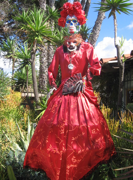 Larger-than-life Day of the Dead mannequin wears a beautiful red dress.