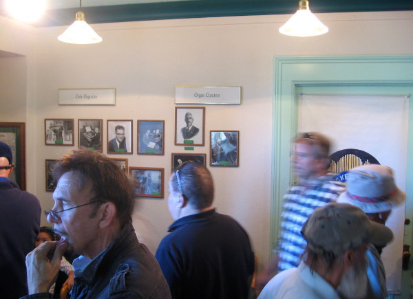 A hallway contains dozens of historical photos of concerts, organists and Balboa Park.