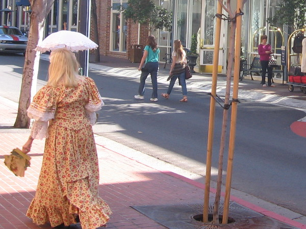 Lady in old-fashioned dress walks with her umbrella past Horton Grand Hotel.