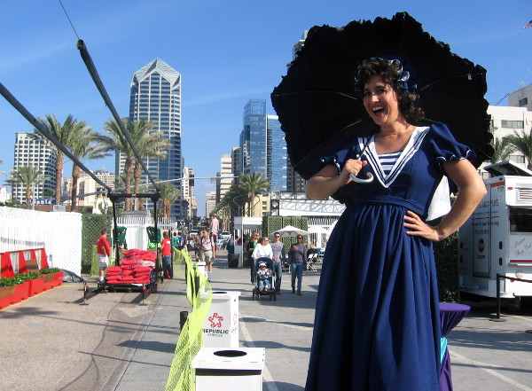 Roving lady stilt walker with parasol welcomes people to Broadway Pier celebration.