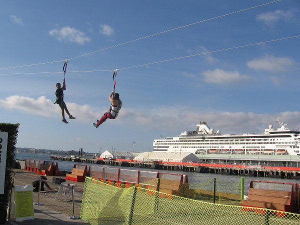 Brave souls soar down a zip-line with a docked cruise ship in background.