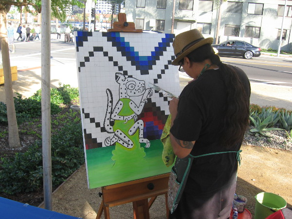Artist of Mexikota Art works on a canvas south of the pier near Harbor Drive.