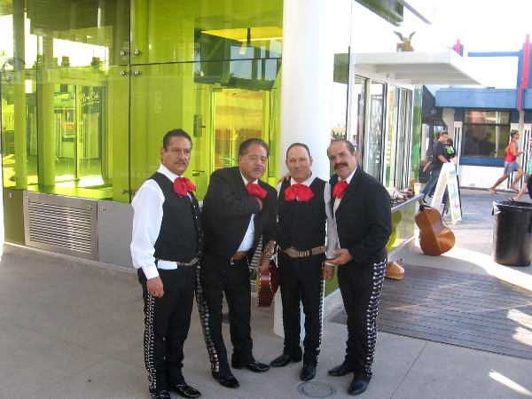 Mariachis take a break between performances near one new colorful pavilion.