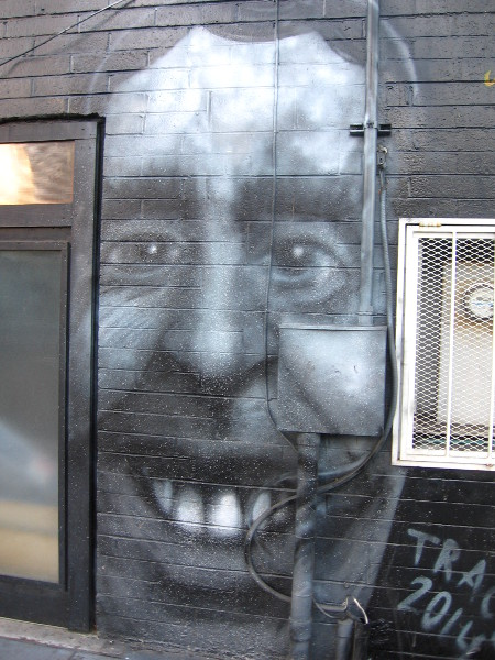 Smiling face painted on building wall on 16th Street in East Village.