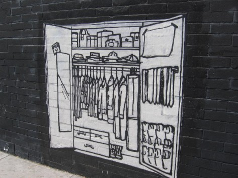 Closet full of clothes opens onto a city sidewalk.