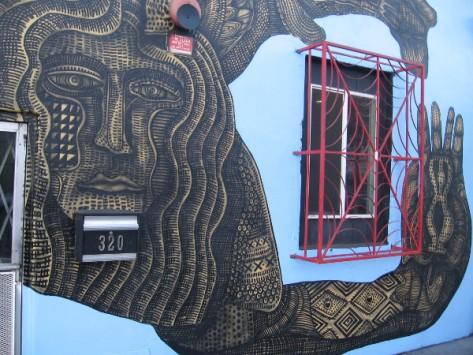 Elaborate figure's arm embraces a building window. Art by Zio Ziegler.