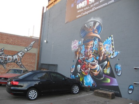 Bold, colorful street art on walls of parking lot behind Undisputed Fitness.