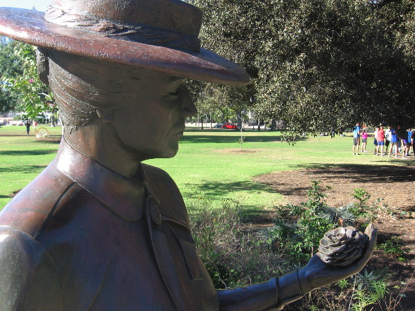 Kate Sessions, the Mother of Balboa Park, holds a pine cone by the grass.