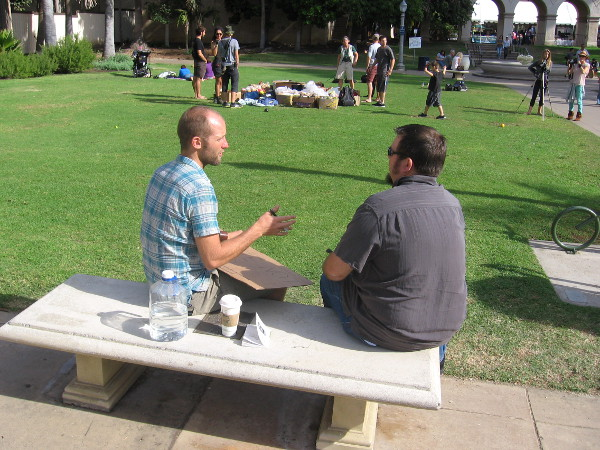 Rob Greenfield explains his goals on a bench, with Casa del Prado arches in the background.