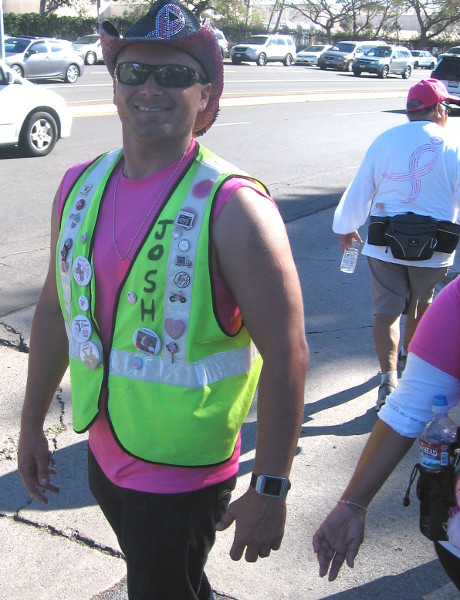 Guy helping with traffic wears pink and lots of pins and buttons.
